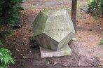 Foto de um dodecaedro em pedra tirada em Berlim, possivelmente utilizado como uma lápide.