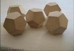 Imagem de cinco dodecaedros de madeira organizados de modo a permitir a observação do poliedro sob diferentes ângulos.