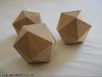 Imagem de três icosaedros de madeira organizados de modo a permitir a observação do poliedro sob diferentes ângulos.
