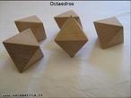 Imagem de cinco octaedros de madeira organizados de modo a permitir a observação do poliedro sob diferentes ângulos.