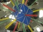 O canudo verde, colocado entre os dois espelhos que formam entre si um ângulo de 90°, mostra os 6 eixos de rotação de ordem 2 do cubo (as retas que passam pelos pontos médios de duas arestas opostas); o canudo vermelho, colocado entre os dois espelhos que formam entre si um ângulo de 45°, mostra os 3 eixos da rotação de ordem 4 do cubo (as retas que passam pelo centros de duas faces opostas). O canudo amarelo, colocado entre os dois espelhos que formam entre si um ângulo de 60°, mostra os 4 eixos de rotação de ordem 3 do cubo (as retas que passam por dois vértices opostos).